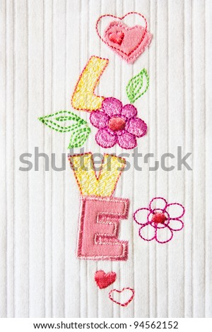 Patchwork embroidered word 'love' with hearts and flowers - stock photo