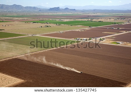 Patchwork of Farmland with tractor kicking up dust - stock photo
