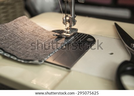 Patchwork sewing technology. Linking pastel cloth patches with sewing machine. A reverse side of a work. - stock photo