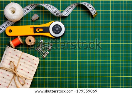 Patchwork sewing tools on green mat - stock photo