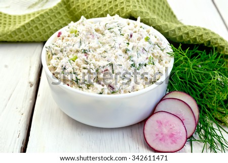 Pate of cottage cheese, dill and radish in a bowl, radish slices, dill and a napkin on a wooden boards background - stock photo