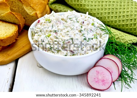 Pate of cottage cheese, dill and radish in a bowl, radish slices, dill, bread and a napkin on a wooden boards background - stock photo