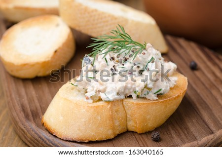 pate of smoked fish with sour cream and dill on toasted bread  - stock photo