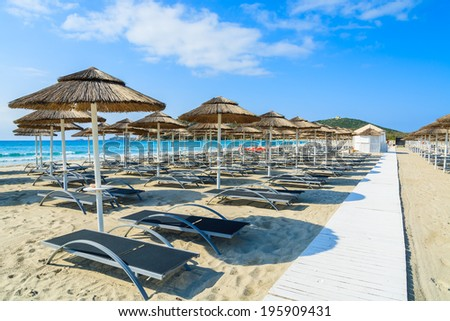 Path along sunchairs with umbrellas on white sand beach in Porto Giunco bay, Sardinia island, Italy - stock photo
