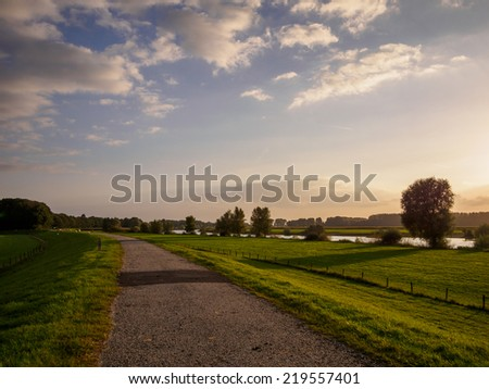 Path along the river Ijssel in Holland be sunset light - stock photo
