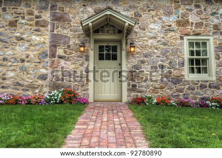 Path and door entrance of a stone home with spring flowers and lush lawn.