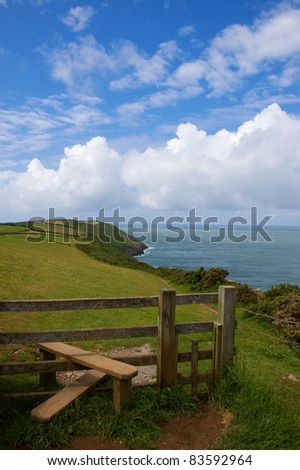 Path and stile on a coastal footpath with the sea and cliffs beyond