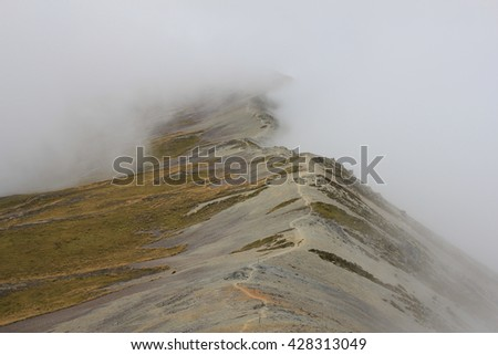 Path following a mountain ridge disapears in fog. Scene on Mt Robert, New Zealand. - stock photo