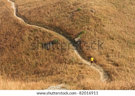path in mountain, and a man walking - stock photo