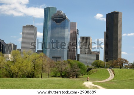 Path in park leading to city skyline - bike visible on path - stock photo