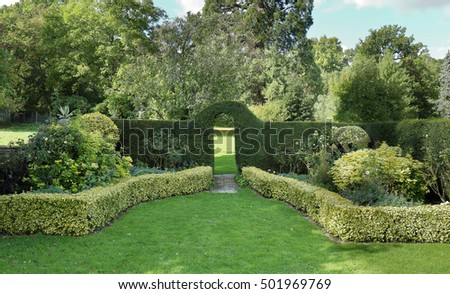 Path leading through an archway in a hedgerow to a lawn beyond