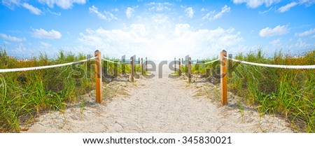Path of sand going to the beach and ocean in Miami Beach Florida , on a beautiful summer morning with blue sky  - stock photo