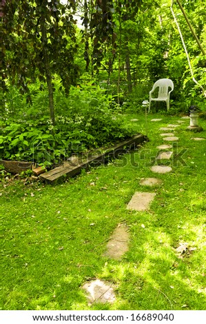 Path of stepping stones leading to secluded corner in lush green garden - stock photo