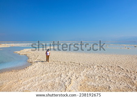 Path of the evaporated salt. The coast of the Dead Sea in Israel. The woman - tourist walks under the bright sun - stock photo