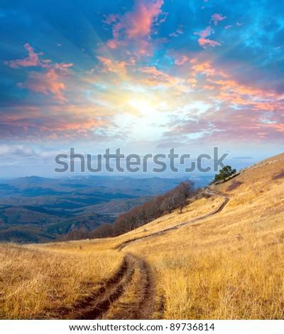 path on mountain meadow under sunset sky - stock photo