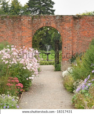 Path through an Arched Gateway to an English Walled Garden - stock photo