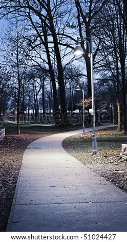 Path through city park at dusk with street lamps - stock photo