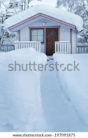 Path through snow going to small house, Kiruna, Lapland, Sweden - stock photo