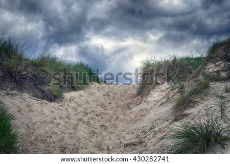 Path through the sand dunes to the beach on the North Sea in Denmark - stock photo