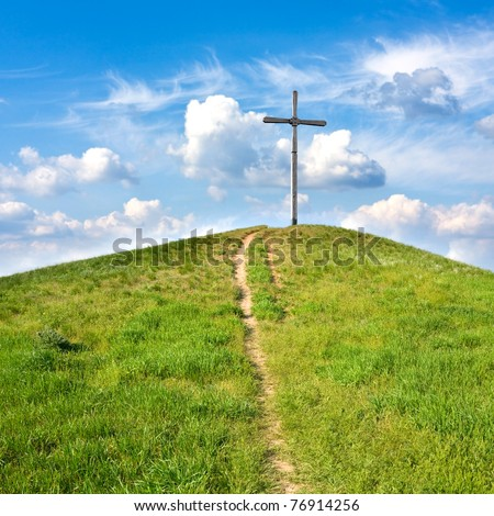 path to cross on hill - stock photo
