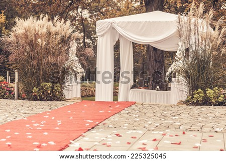 path to wedding ceremony marquee with petals, vintage picture - stock photo