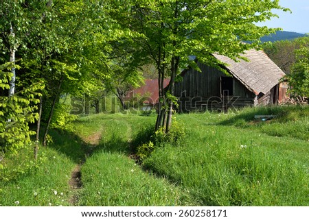 Path way and old barn situated on a hilly meadow - stock photo