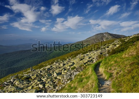 paths in the mountains of the Carpathians in front old polish observatory stones overgrown with moss right - stock photo