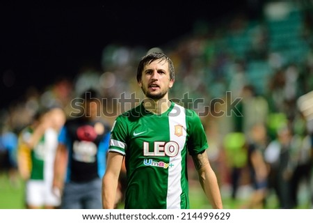 PATHUMTHANI,THAILAND Aug 23 : Darko Tasevski(green 22) of BGFC in action during geam Thai premier League 2014 between Bangkok Glass FC and TOT SC at LeoStadium on AUGUST 23, 2014 in Thailand - stock photo