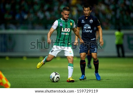 PATHUMTHANI,THAILAND-20 JULY:Teeratep Winothai  #14 (L) of Bangkok Glass fc. in action during Thai Premier League between Bangkok Glass fc.and Burirum Utd.at Leo Stadium on July 20,2013 in Thailand - stock photo