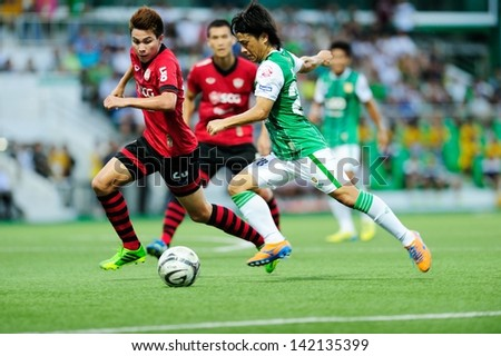 PATHUMTHANI,THAILAND JUN 2013 : Hironori Saruta(green) of BGFC in action during Thai premier League 2013 between Bangkok Glass FC and SCG MUANGTHONG UNITED at LeoStadium on JUNE 9, 2013 in Thailand - stock photo