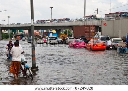 PATHUMTHANI, THAILAND - OCTOBER 18 -Thai flood hits Central of Thailand, higher water levels expected, cars and bicycle navigating through the flood- Tuesday october 18, 2011 in Pathumthani, Thailand - stock photo
