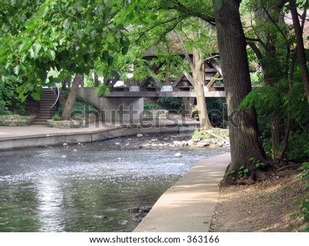pathway along river with trees and covered bridge in background - stock photo