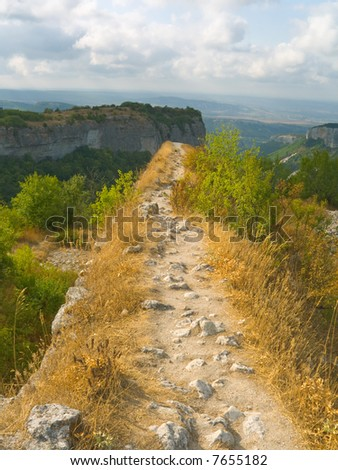 Pathway and precipice in mountains, cloudy sky - stock photo