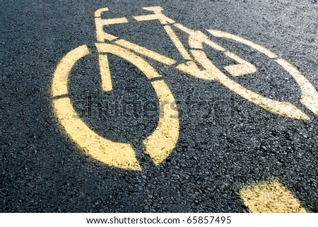pathway for bicycle with yellow bicycle lane sign on road - stock photo