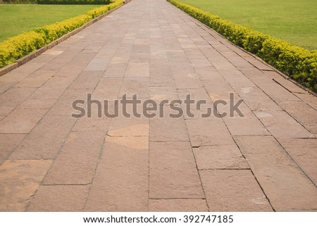 Pathway formed slabs stone between land with fresh green spring or summer grass in a garden park central city town Empty space for full length walking or standing people - stock photo