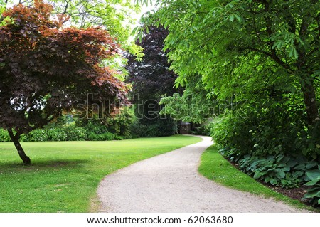 Pathway in a Peaceful Green Garden - stock photo
