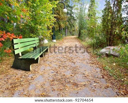 Pathway with the bench at the beginning of the autumn - stock photo
