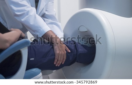 Patient and Doctor in fully open high field Magnetic Resonance Image MRI CAT Scan scanning knee and leg.