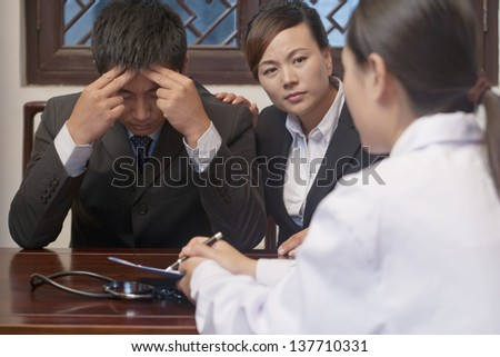 Patient and Spouse Concerned about Doctor's Results - stock photo
