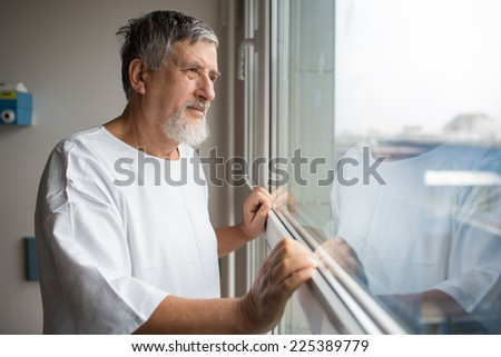 Patient at a hospital, looking from a window in his room, doing much better after the surgery - stock photo