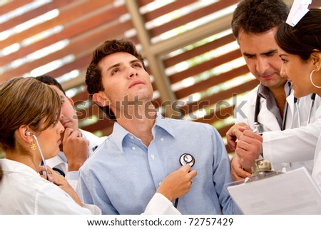 Patient at the hospital with a group of doctors around