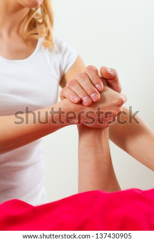 Patient at the physiotherapy doing physical therapy exercises with his therapist - stock photo