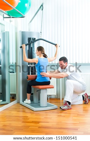 Patient at the physiotherapy or physical therapy doing exercises with her therapist - stock photo