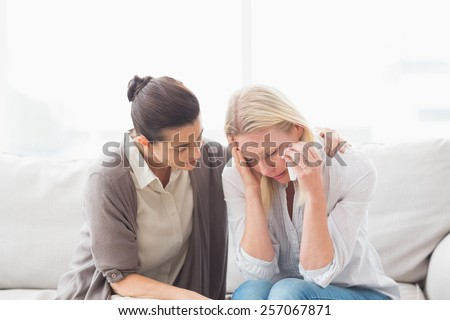 Patient crying next to her therapist while she is comforting her - stock photo