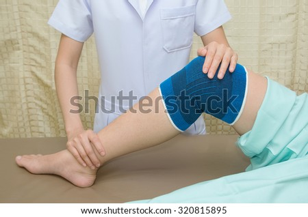 Patient  doing physical exercises with physical therapist ,  in rehabilitation clinic - stock photo