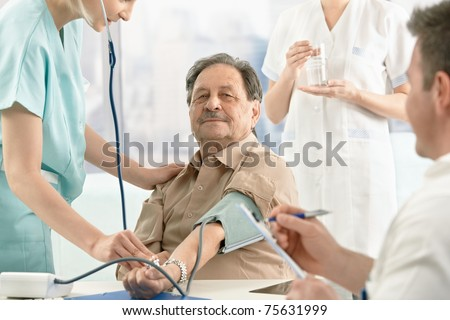Patient getting blood pressure measurement, nurse and doctor examining.?