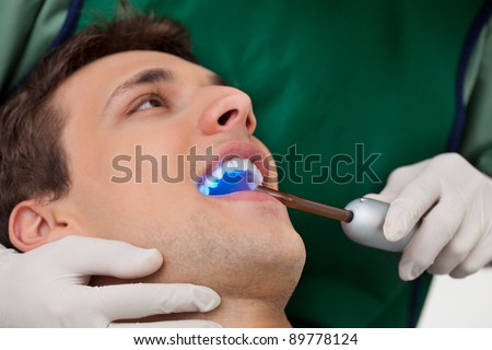 Patient having dental checkup with ultraviolet light at dentist's clinic - stock photo