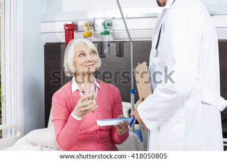 Patient Holding Water Glass And Medicine While Looking At Doctor - stock photo
