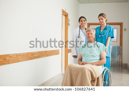 Patient in a wheelchair next to nurses in hospital - stock photo