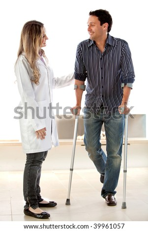 Patient in crutches talking to a doctor - stock photo